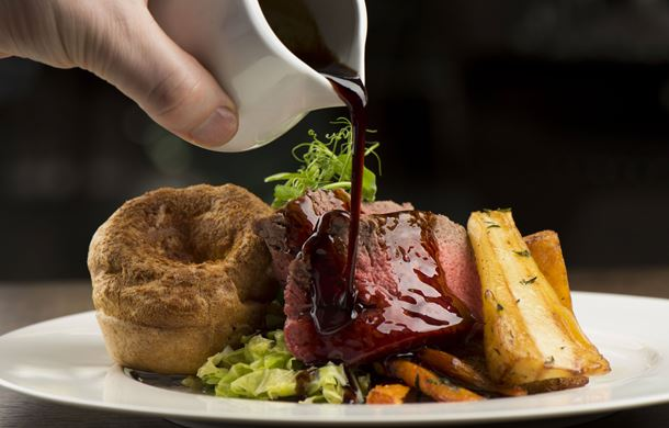 Gravy being poured over roast sirloin of Welsh beef, roasted root vegetables and Yorkshire pudding,