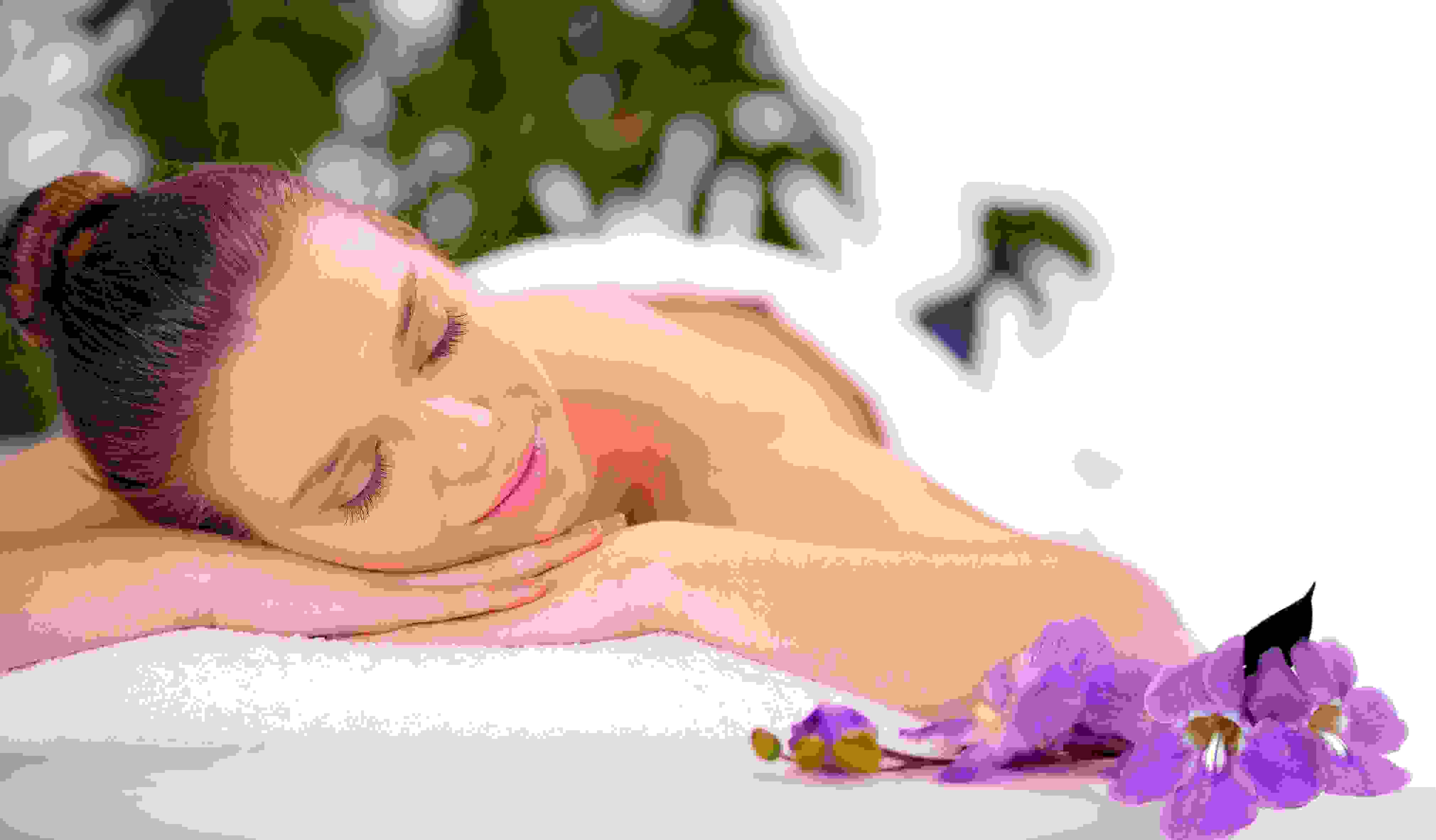 Lady relaxing in the Vale Spa next to purple flowers