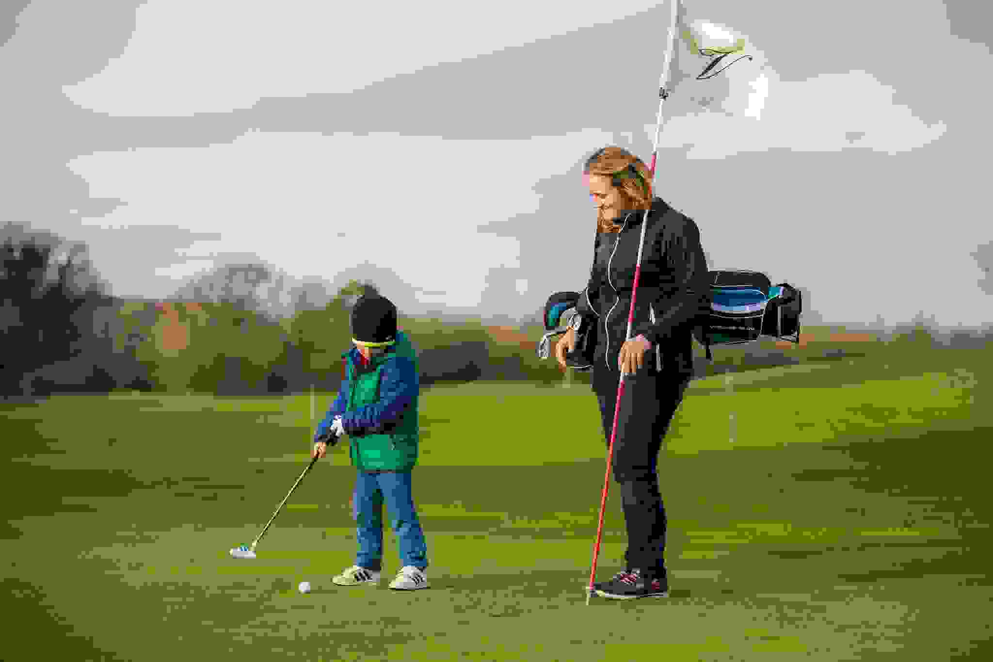 Golf pro coaching young boy at the Vale Resort