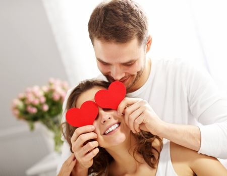 Man holding heart shaped card in front of woman's eyes