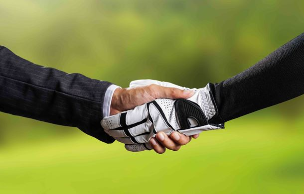 Man in suit shaking hands with golfer