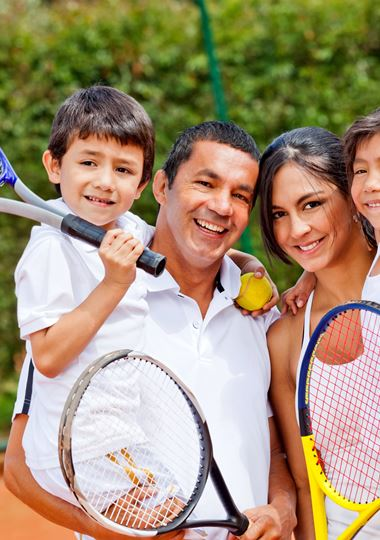 Family holding tennis rackets