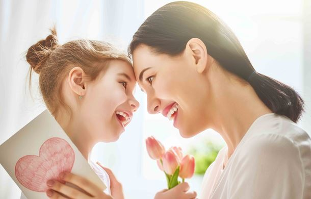 Mother and daughter holding card and flowers