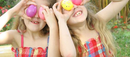 Two young girls holding eggs up to their eyes