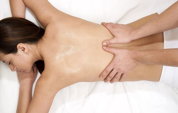 Therapist massaging woman's back